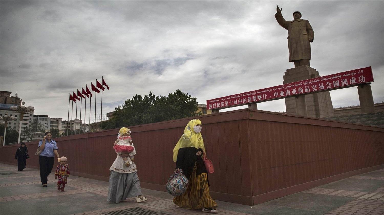 Hai phụ nữ Hồi giáo Duy Ngô Nhĩ đi ngang qua tượng đài Mao Trạch Đông ở thành phố Kashgar, Tân Cương năm 2014. (Ảnh qua IQSoft Software Consultants)