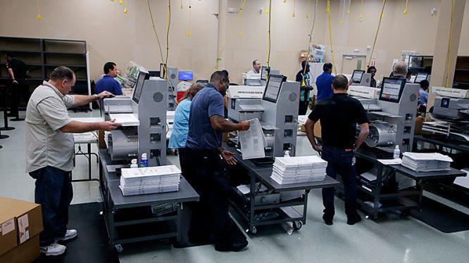 Nhân viên kiểm phiếu bỏ phiếu vào máy kiểm phiếu, khi kiểm lại phiếu ở Văn phòng giám sát bầu cử quận Broward ở Lauderhill, Florida, ngày 11/11/2018.