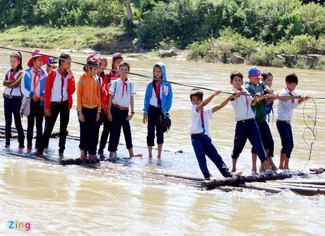 Học sinh ở Quảng Ngãi mạo hiểm đi bè qua sông, do quá tải nên các em phải xắn quần lên cho khỏi ướt. (Ảnh qua News.Zing.vn)
