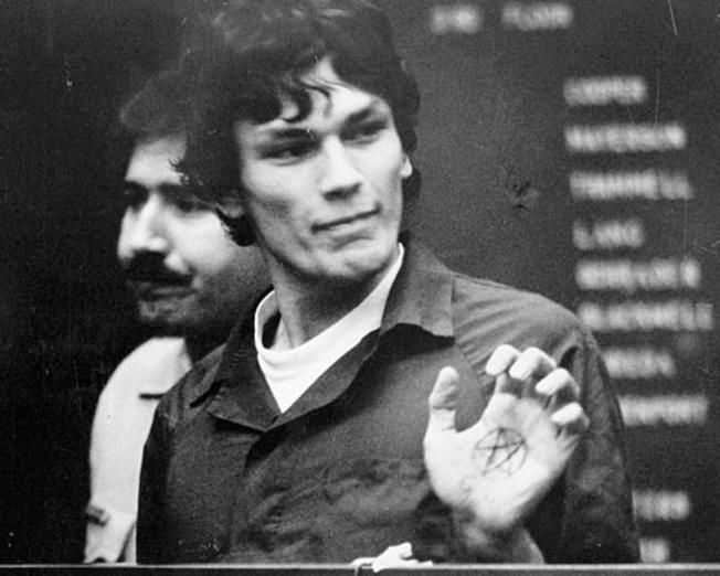 Richard Ramirez trưng ký hiệu sao 5 cánh xăm trong lòng bàn tay tại phòng xử án. (Ảnh qua Nbclosangeles)