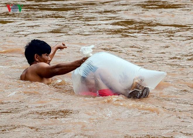 Hình ảnh học sinh chui túi nylon băng qua suối. Ảnh: VOV.