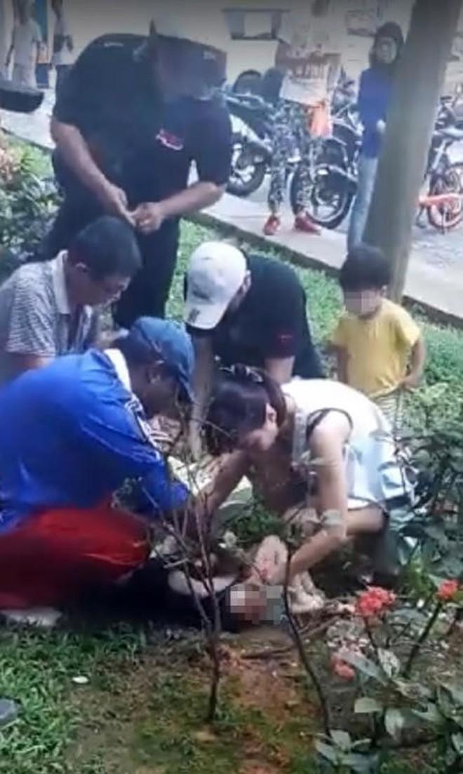 Người dân phát hiện cậu bé nằm trên bãi cỏ dưới chân tòa nhà ở Sengkang, Singapore sáng 25/11. Ảnh: Straits Times.