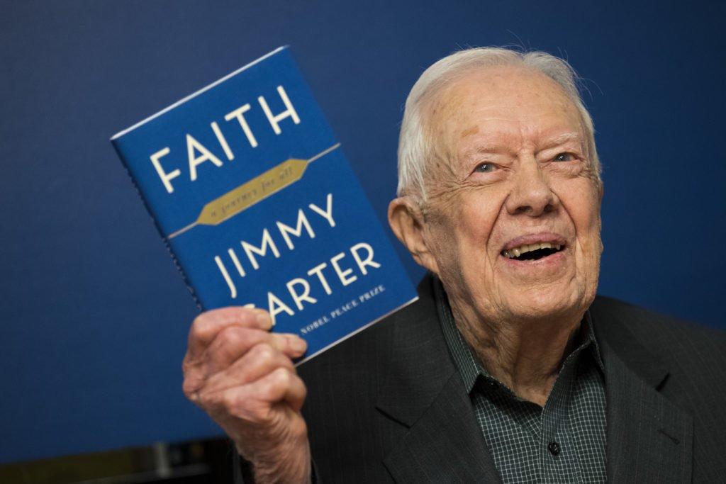 """Cựu Tổng thống Jimmy Carter và cuốn sách """"Faith – A Journey For All""""của ông. (Ảnh quaTwitter)"""