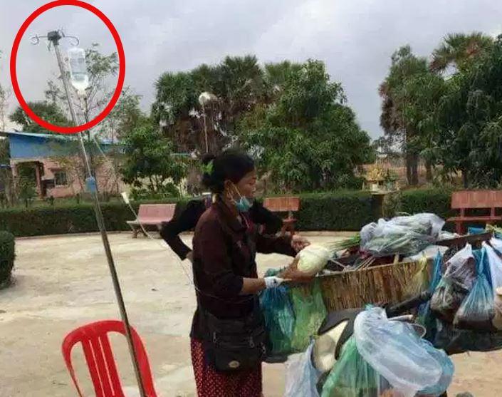 Xúc động hình ảnh người phụ nữ vừa truyền dịch, vừa bán rau giữa đường - H1