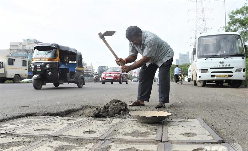 Bận rộn với công việc buôn bán nhưng người cha 49 tuổi vẫn cần mẫn đi lấp kín những ổ gà trên đường. (Ảnh qua The Citizen)