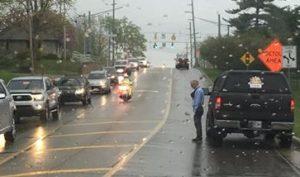 Người đàn ông đứng dưới mưa, cúi đầu thành kính trước đám tang của một người lạ