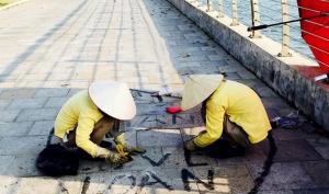 Cặp đôi thể hiện tình yêu trên vỉa hè, 2 nữ công nhân vất vả tẩy hình vẽ bậy giữa nắng gắt