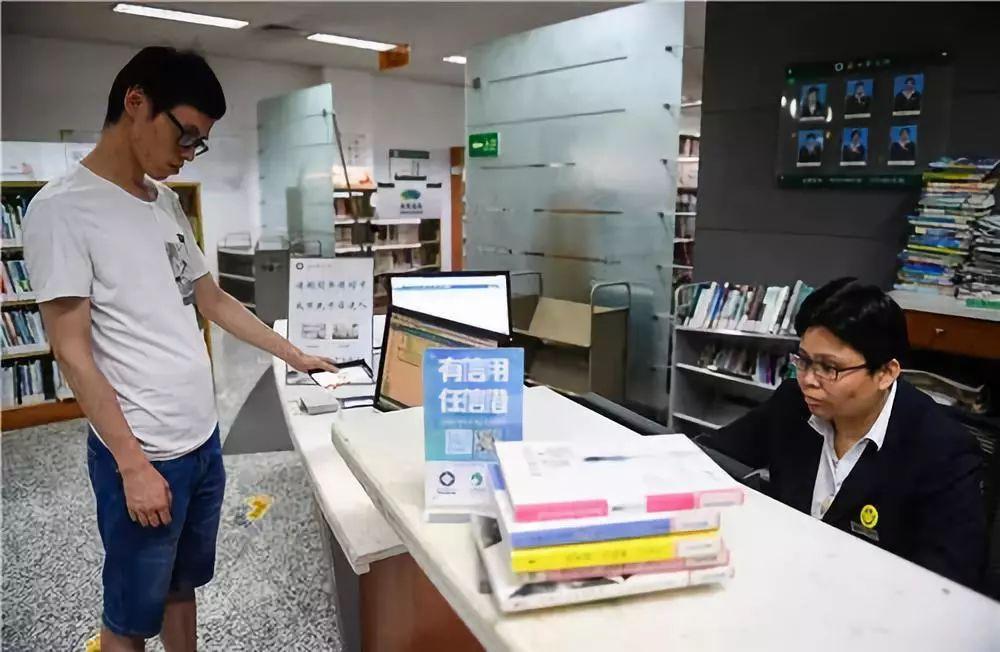 Một người dân ở Tô Châu trình điểm số tín nhiệm công dân của mình để được mượn sách nhiều hơn và nhanh hơn. Ảnh: Caixin.