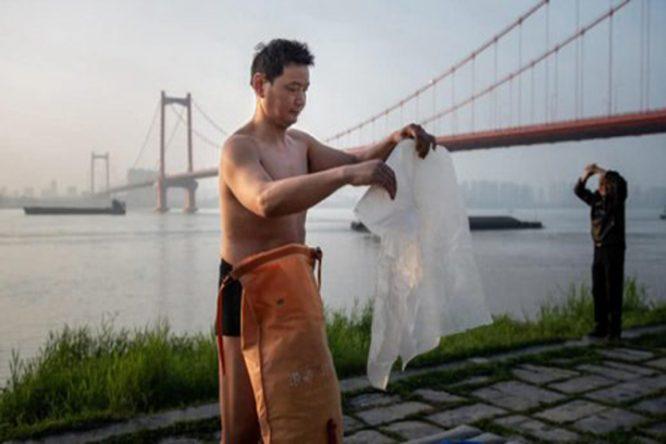 Ông Zhu chuẩn bị túi đồ trước khi vượt sông. (Ảnh qua VnExpress.net)