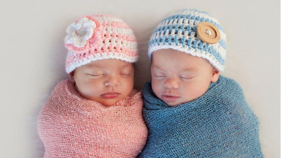 Cặp song sinh năm tuần tuổi với trang phục hồng và xanh. Bạn có biết đâu là trai, đâu là gái?
