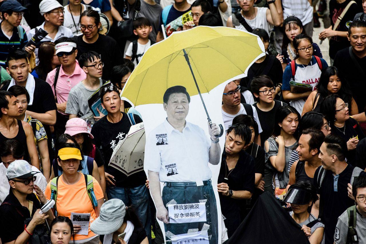 """Có thể nói cuộc biểu tình của người Hong Kong phản đối luật dẫn độ của Trung Quốc đại lục là sự kiện chính trị nổi bật năm 2019. Người dân Hong Kong biểu tình hôm thứ 7, ngày 15/6 và mang theo tấm bình cứng in hình Chủ tịch Trung Quốc Tập Cận Bình cầm một chiếc ô màu vàng - biểu tượng của """"Phong trào ô dù"""" dân chủ ở Hong Kong. (Ảnh: AFP-JIJI)"""