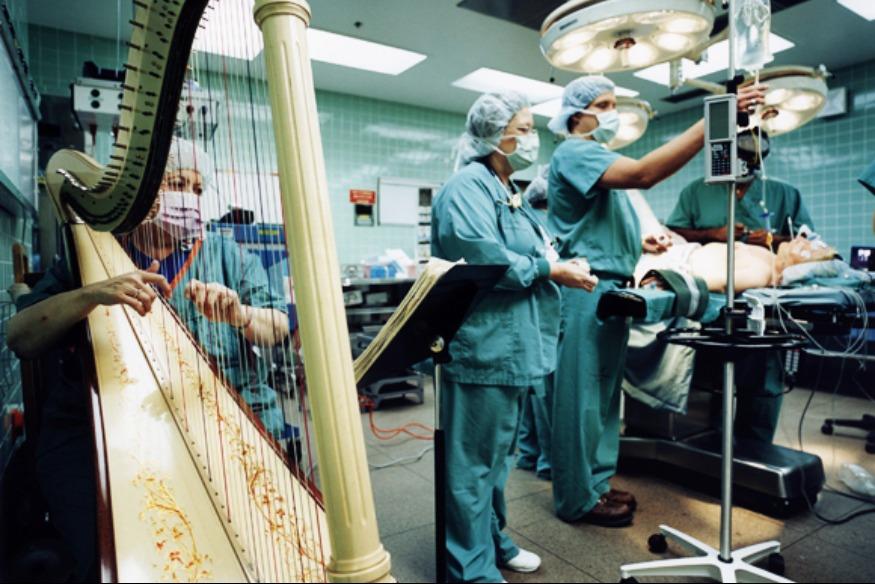 Nhà trị liệu âm nhạc chơi đàn hạc trong phòng phẫu thuật để bệnh nhân giảm căng thẳng. (Ảnh qua theriverofcalm.com)