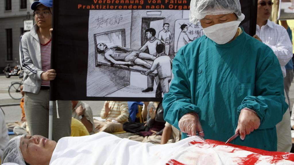 Trong sự kiện phản đối mổ cướp nội tạng ở Berlin, Đức, một người mặc đóng vai bác sĩ Trung Quốc mô phỏng lại việc học viên Pháp Luân Công bị mổ cướp nội tạng. (Ảnh: Getty Images)