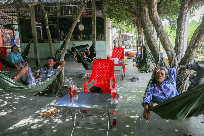 Nhiều vị khách là những người lao động đến quán cà phê cây si này để tránh nóng.