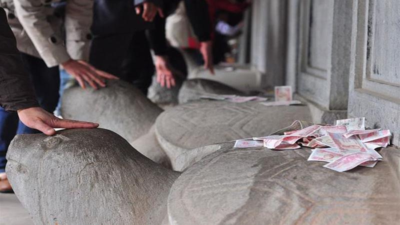 Xoa đầu rùa, vứt tiền bừa bãi lên bia đá tại Quốc Tử Giám.