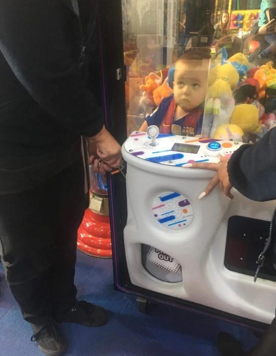 Không dám xin mẹ, cậu bé chui vào máy gắp thú lấy thú bông rồi bị mắc kẹt.1
