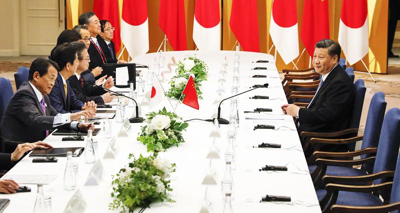 Ông Tập lẻ loi ngồi ở một bên dãy bàn hội nghị đối diện với ông Abe và các quan chức Nhật Bản khác chỉ vì đoàn đại biểu Trung Quốc đến muộn.