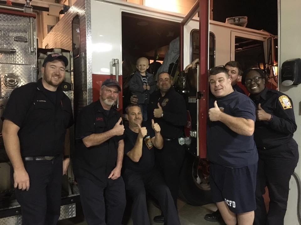 Nolan chụp ảnh chung với đồng nghiệp của bố ở sở cứu hỏa.