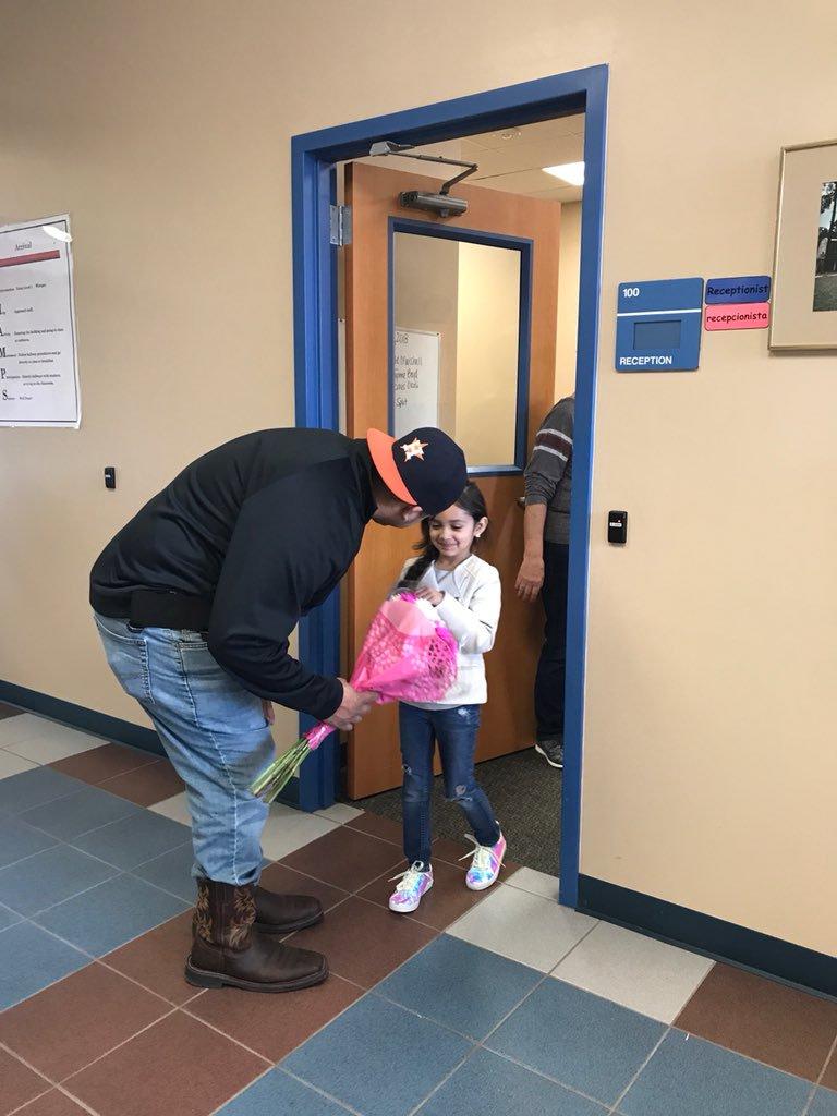Cha cô bé tranh thủ chút thời gian trong giờ làm để đến tận phòng học tặng hoa cho con gái. (Ảnh qua Twitter)