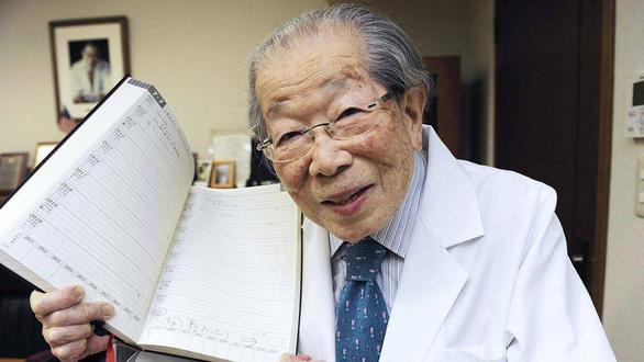 Cụ Hinohara giơ cuốn sổ khám bệnh để dành chỗ trống cho lịch khám 5 năm tiếp theo. Có lẽ cụ là một trong những bác sĩ, nhà giáo lớn tuổi nhất thế giới bởi đến vài tháng trước khi mất, ông vẫn còn khám cho bệnh nhân. (Ảnh: meddybear.net)