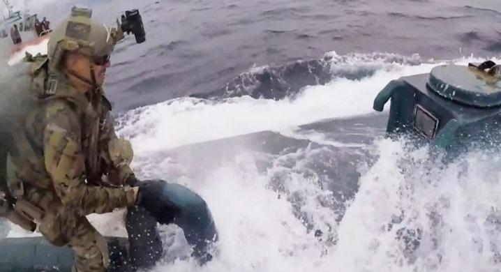hai sĩ quan nhảy lên tàu và một người lao thẳng tới cửa nóc trên tàu ngầm chở ma túy