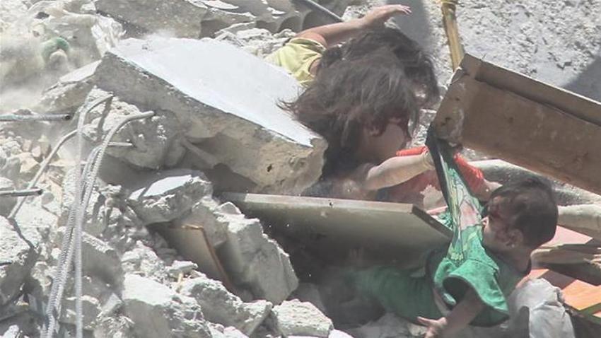 Cô bé Riham al-Abdullah với tay nắm lấy em gái Tuqa bên mé ngôi nhà đổ nát do bị trúng tên lửa ở Ariha, tỉnh Idlib hôm 24/7. (Ảnh: SY-24)