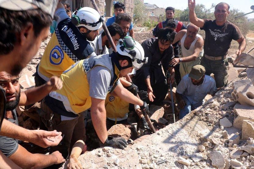 Những người cứu hộ đang tìm kiếm các nạn nhân dưới đống đổ nát của một tòa nhà bị phá hủy do không kích ở Syria. (Ảnh qua .sbs.com.au)