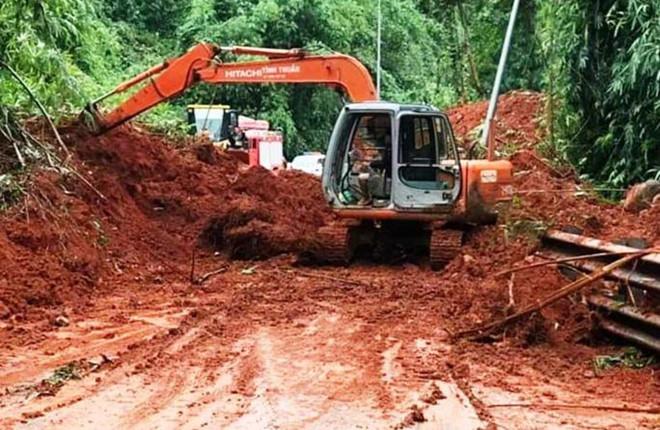 Cơ quan chức năng điều máy múc đến hiện trường giải phóng đất đá đổ xuống đường.