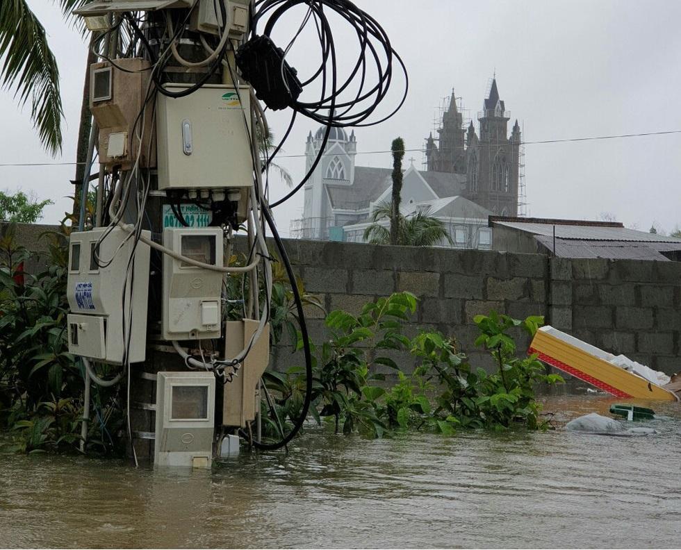 Nước ngập cả trụ điện khiến Điện lực Phú Quốc phải cúp điện chờ nước rút. (Ảnh qua tuoitre)
