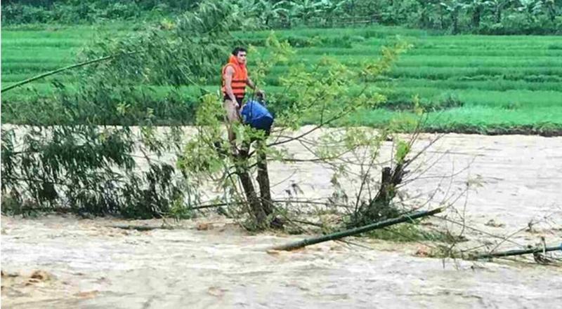 Thấy tình hình khẩn cấp, anh Huy đã quyết định nhảy xuống dòng nước lũ tiếp cận, đưa ông Lương Văn Chon vào bờ an toàn. (Ảnh qua nld)