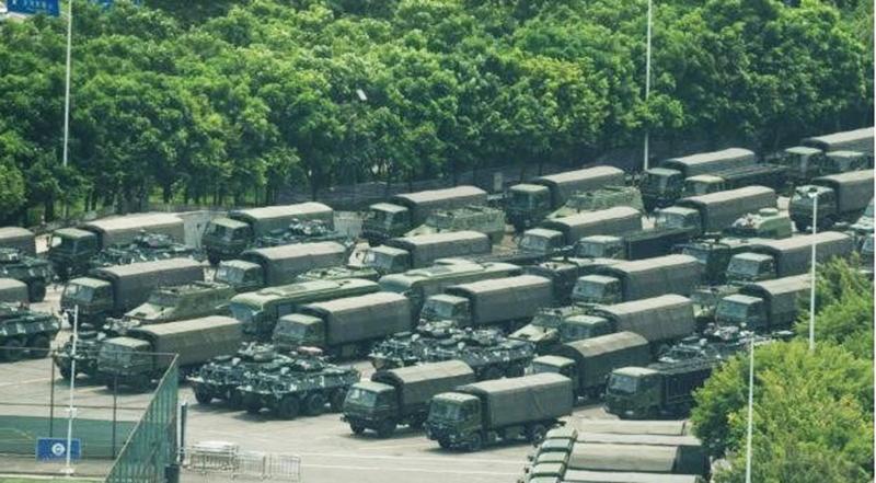 Xe tải và xe bọc thép chở quân bên ngoài sân vận động Vịnh Thâm Quyến hôm 15/8. (Ảnh qua Zing)