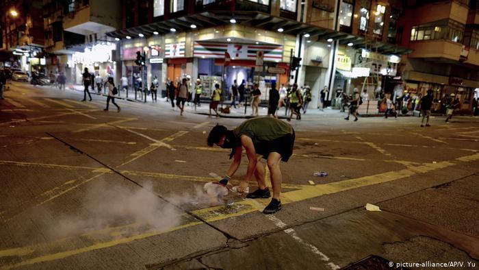 Một người biểu tình đang cố gắng dập tắt một quả bom hơi cay. (Ảnh qua dw)