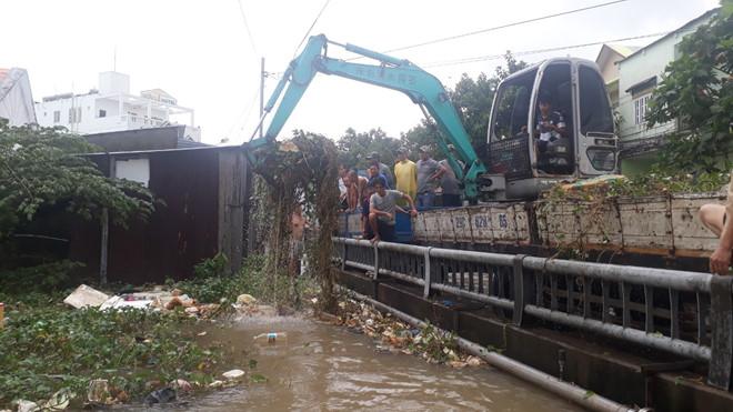 Người dân huy động xe cuốc đất để móc rác dưới rạch Ông Trì.