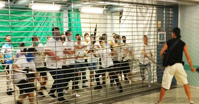 Một nhóm đàn ông mặc áo trắng cố gắng mở cửa tại nhà ga Nguyên Lãng, Hồng Kông. (Ảnh: Handout)