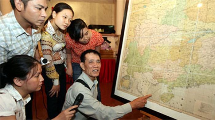 Tiến sĩ Mai Hồng giải thích cho người xem nội dung chữ Hán cổ trên bản đồ của Trung Quốc năm 1904 mà ông đã hiến tặng Bảo tàng Lịch sử quốc gia sáng 25/7. (Ảnh qua tuoitre)