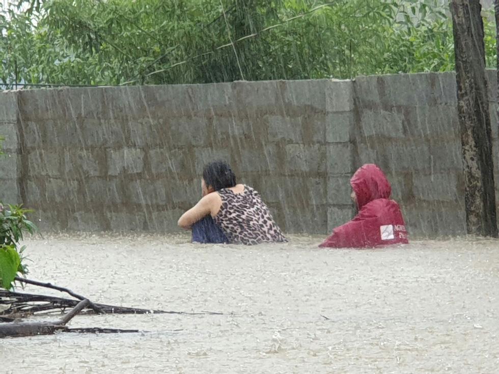 Người dân lội trong dòng nước ngập ngang lưng để tìm chỗ trú.