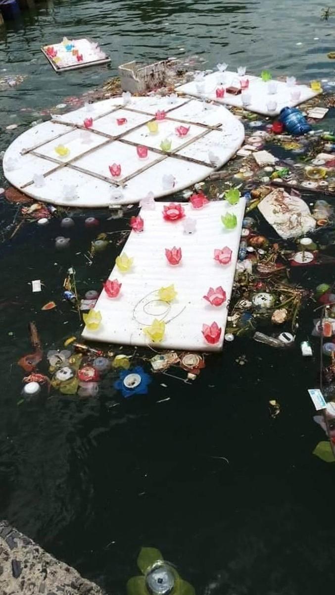 Hình ảnh đèn hoa đăng bằng nhựa trôi nổi lẫn với rác thải gây ô nhiêm môi trường trên vịnh.