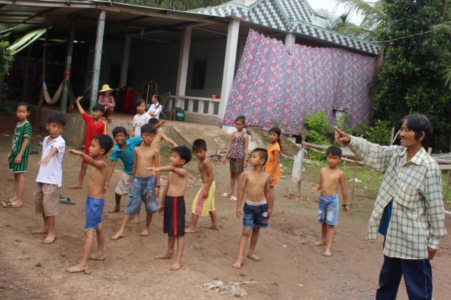 Trước khi tập bơi, bà cho lũ trẻ tập các động tác khởi động cho nóng người trước.