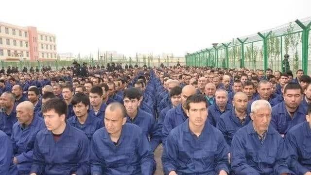 Gần 1000 người mặc áo tù nhân ngồi ngay ngắn bên trong hàng rào lưới sắt của một trại tập trung ở Tân Cương (Ảnh qua Twitter)