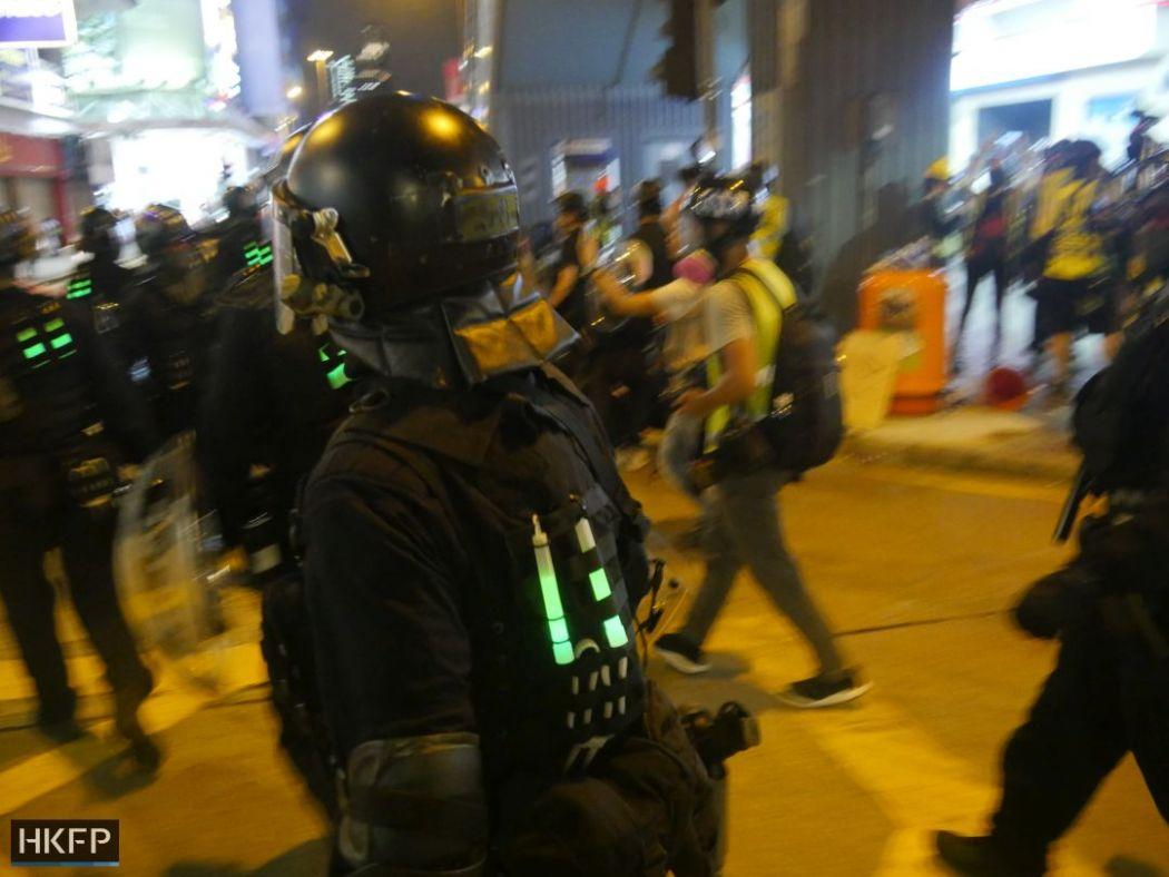 Một người giả dạng người biểu tình mang theo gậy phát sáng màu xanh để dễ nhận dạng. (Ảnh: HKFP).