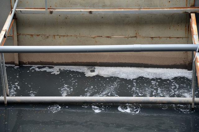 Có thể thấy được rất rõ bên ngoài khu vực các bể nước làm thí điểm xử lý, dòng nước sông Tô Lịch đang chảy vẫn đen kịt