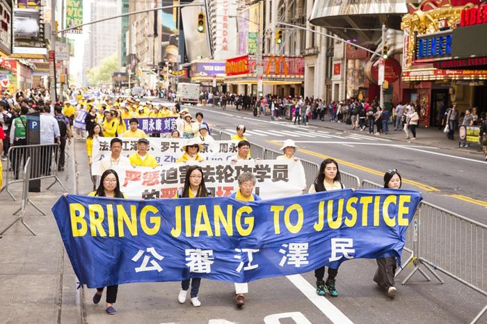 """Biểu ngữ """"Đưa Giang ra công lý"""" trong một cuộc diễu hành phản đối cuộc đàn áp của các học viên Pháp Luân Công."""