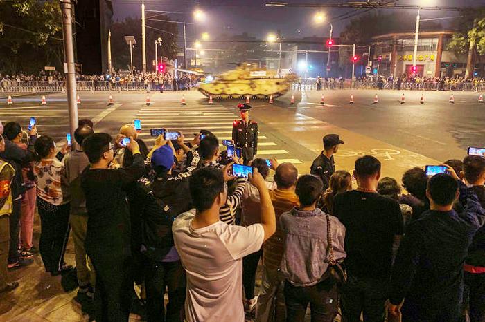 Người dân thủ đô Bắc Kinh theo dõi xe tăng quân sự lăn bánh trong lễ tập duyệt sáng sớm 22/9.
