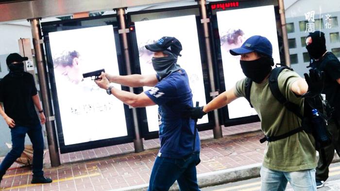 Trong một cuộc đụng độ giữa cảnh sát và người dân, có người được cho là cảnh sát chìm, rút súng ngắn hướng vào người biểu tình.