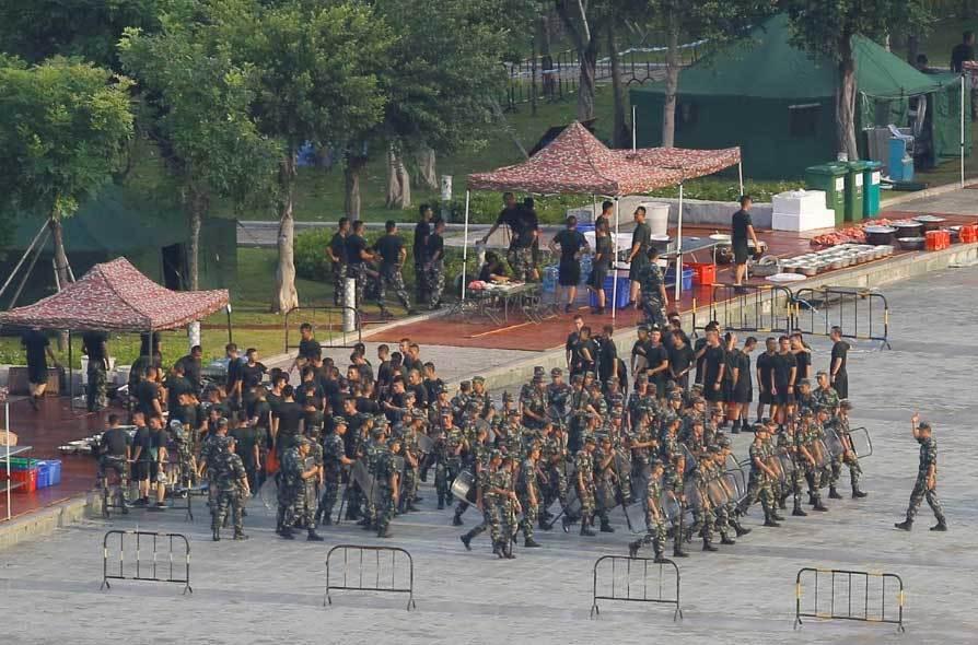 Hàng nghìn quân nhân Trung Quốc vẫy cờ đỏ diễu binh tại một sân vận động ở Thâm Quyến, phía bờ đối diện với Hông Kông.