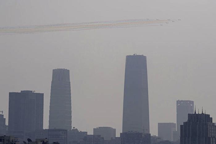 Máy bay trực thăng tạo hình trong lễ diễu binh, trên nền trời mù mịt.