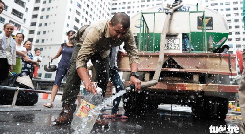 Người dân khu HH đô thị Linh Đàm (Hoàng Mai, Hà Nội) lấy nước từ xe bồn do ban quản lý tòa nhà cung cấp làm mẫu thử chất lượng nước.