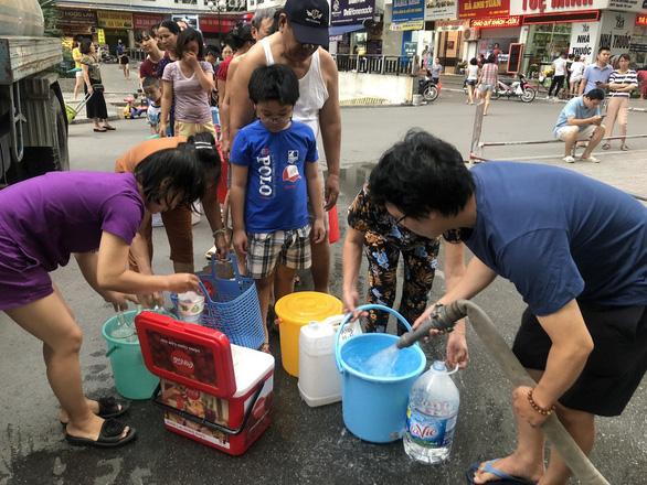 Người dân phải xếp hàng lấy nước sạch trong thời gian chờ nhà máy Sông Đà súc xả đường ống. (Ảnh qua tuoitre)