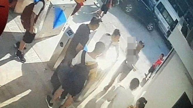 Ảnh chụp màn hình camera lúc một người đàn ông đưa Long vào trường sau khi được phát hiện em nằm ngất trong ô tô. (Ảnh qua bbc)