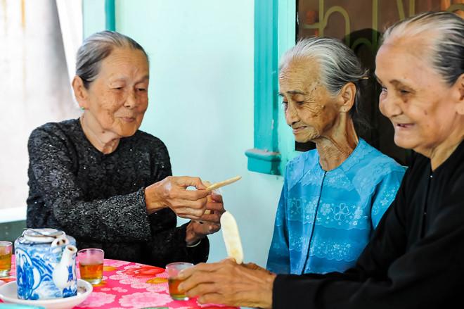 Các cụ bà mời nhau ăn bánh và trò chuyện.